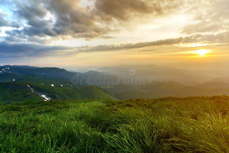 Ευρεία θερινή θέα βουνού στην ανατολή Καμμένος πορτοκαλής ήλιος που αυξάνει στον μπλε νεφελώδη ουρανό πέρα από την πράσινη χλοώδη στοκ εικόνες