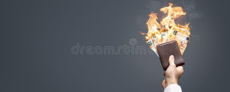 Ευρο- λογαριασμοί σε ένα πορτοφόλι που καίει με μια φωτεινή φλόγα ως πανόραμα στοκ εικόνες