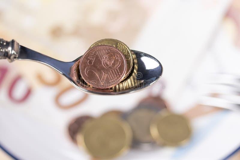 Ευρο- νομίσματα σε ένα κουτάλι επιδορπίων πέρα από ένα πιάτο των χρημάτων με μπλε σύνορα στοκ εικόνα με δικαίωμα ελεύθερης χρήσης