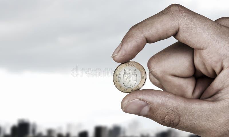 Ευρο- νόμισμα πέντε μεταξύ των δάχτυλων Μικτά μέσα στοκ φωτογραφία