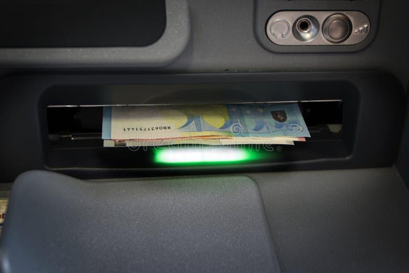 Ευρο- τραπεζογραμμάτια στην αυλάκωση του ATM, έτοιμη να πάρει έξω, μεταξύ του τ στοκ φωτογραφίες