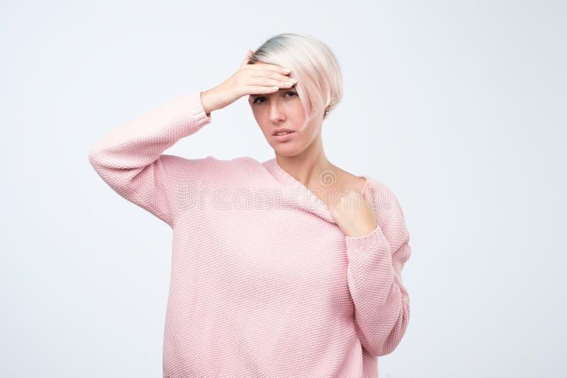 Ευρωπαία γυναίκα ασθένειας στο ρόδινο πουλόβερ που κρατά το χέρι της στο κεφάλι που αισθάνεται άρρωστο στοκ φωτογραφίες με δικαίωμα ελεύθερης χρήσης
