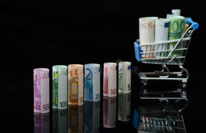 Ευρωπαϊκά χρήματα εγγράφου στους ρόλους και το κάρρο αγορών στοκ εικόνες