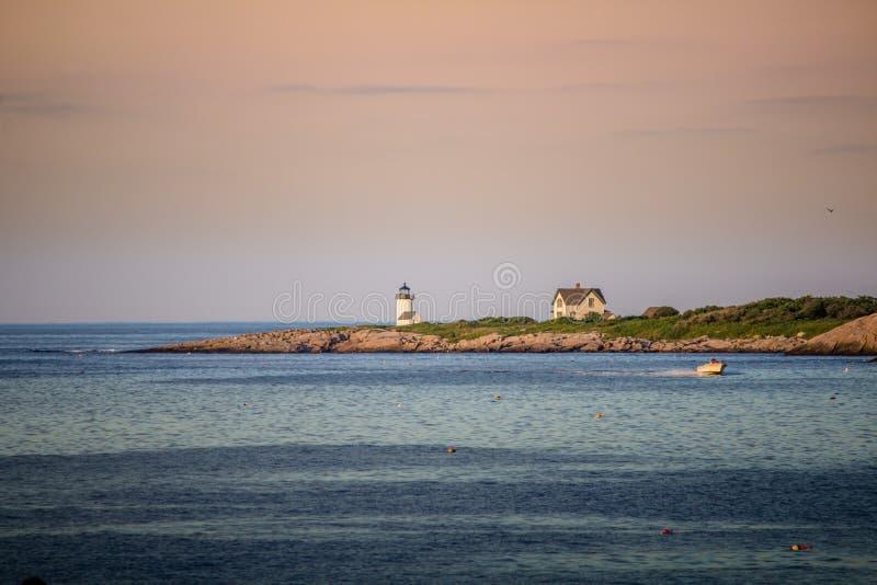Ευρύς πυροβολισμός μιας όμορφης θάλασσας με ένα έδαφος στην πλευρά με τα σπίτια και έναν φάρο στην απόσταση στοκ φωτογραφία