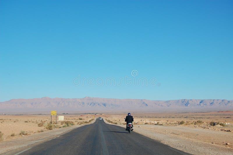 Ευρύς πυροβολισμός της μοτοσικλέτας που οδηγά σε έναν δρόμο στη μέση της ερήμου μια ηλιόλουστη ημέρα με τα βουνά στοκ φωτογραφία με δικαίωμα ελεύθερης χρήσης