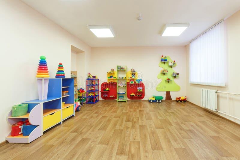 Ευρύχωρο ανοικτό ροζ χρωματισμένο δωμάτιο παιχνιδιών με στον παιδικό σταθμό στοκ εικόνες
