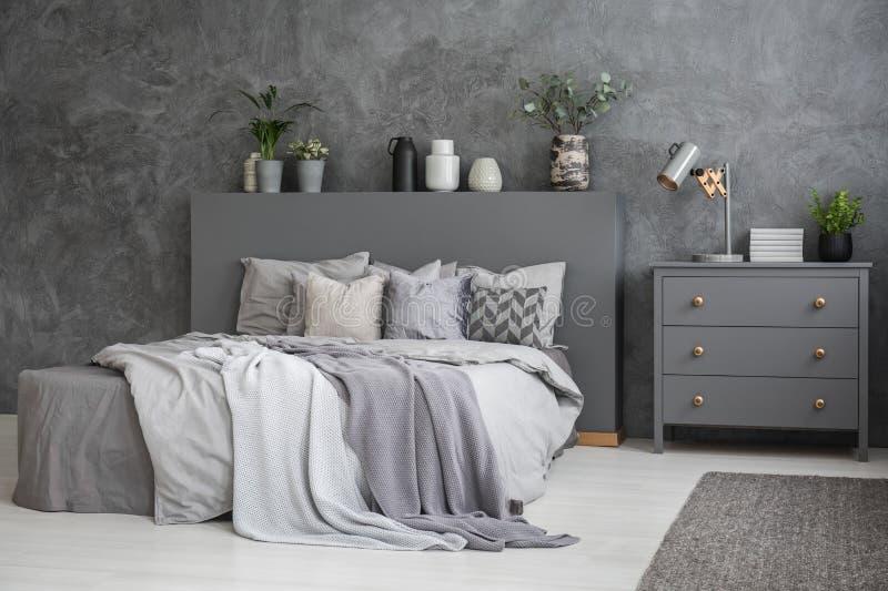 Ευρύχωρο γκρίζο και άσπρο εσωτερικό κρεβατοκάμαρων με το μεγάλο κρεβάτι με το κρεβάτι στοκ εικόνες