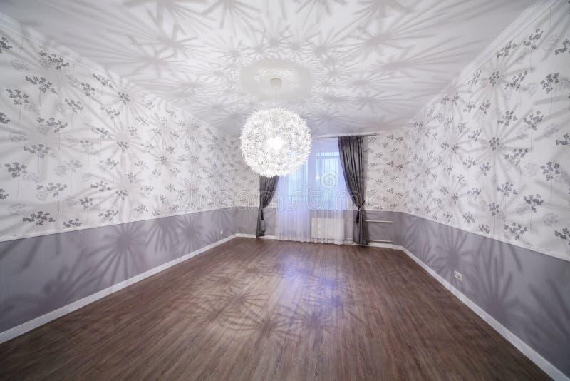 Ευρύχωρο ελαφρύ δωμάτιο με το ξύλινο πάτωμα και τον ασυνήθιστο πολυέλαιο στοκ εικόνα με δικαίωμα ελεύθερης χρήσης