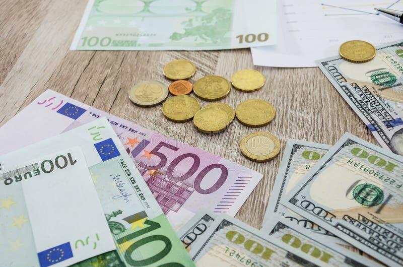 Ευρώ, δολάρια, νομίσματα στον πίνακα στοκ εικόνες