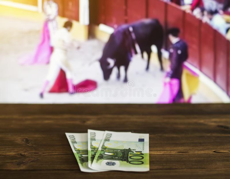 Ευρώ χρημάτων στο υπόβαθρο μιας TV στην οποία παρουσιάστε ταυρομαχία, αθλητική στοιχημάτιση, ευρο- στοκ φωτογραφίες