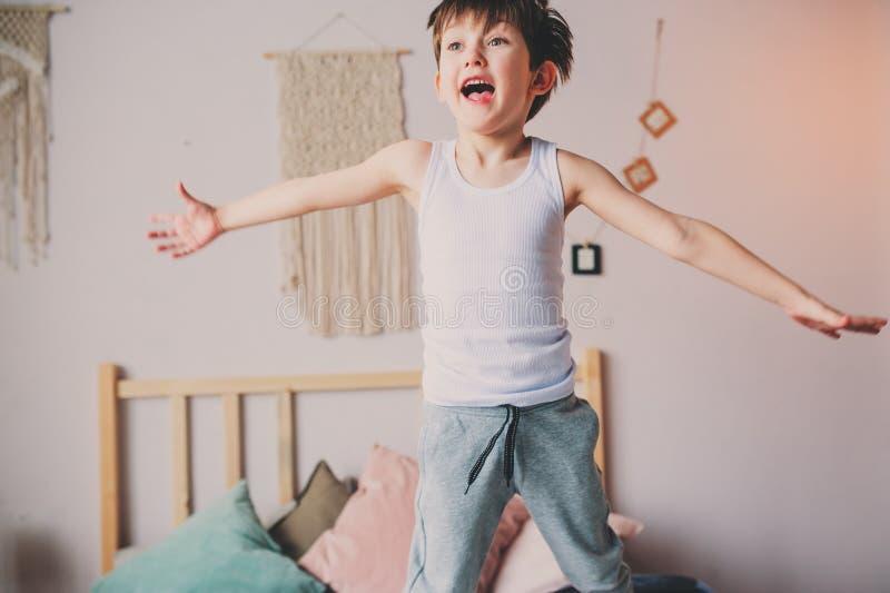 Ευτυχές άτακτο αγόρι που πηδά στο κρεβάτι στα ξημερώματα στοκ φωτογραφίες