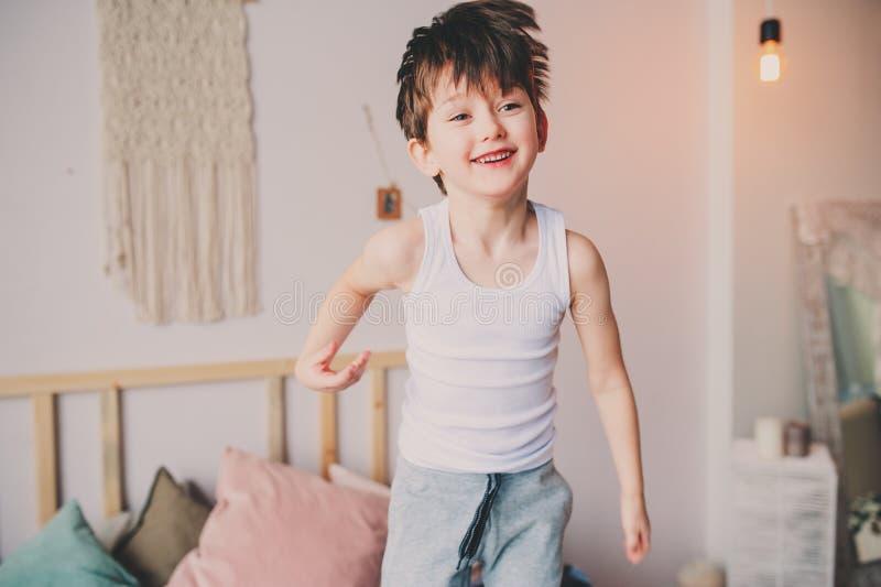 Ευτυχές άτακτο αγόρι που πηδά στο κρεβάτι στα ξημερώματα στοκ φωτογραφία με δικαίωμα ελεύθερης χρήσης
