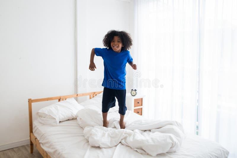Ευτυχές άτακτο παιδί αφροαμερικάνων που πηδά στο κρεβάτι με την ευτυχία στοκ φωτογραφία