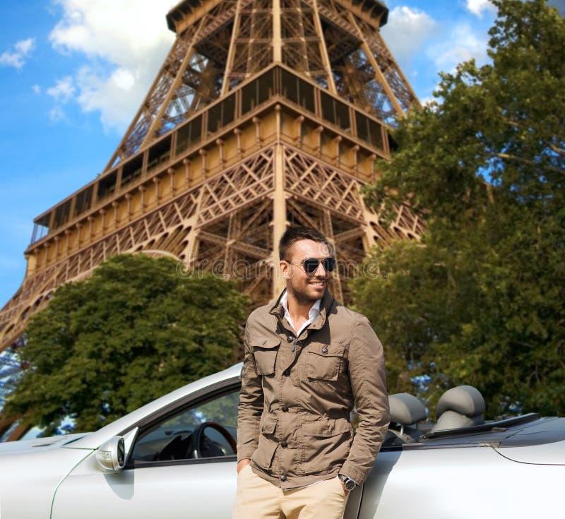 Ευτυχές άτομο κοντά στο αυτοκίνητο καμπριολέ πέρα από τον πύργο του Άιφελ στοκ φωτογραφία με δικαίωμα ελεύθερης χρήσης