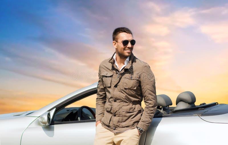 Ευτυχές άτομο κοντά στο μετατρέψιμο αυτοκίνητο πέρα από τον ουρανό στοκ φωτογραφίες με δικαίωμα ελεύθερης χρήσης