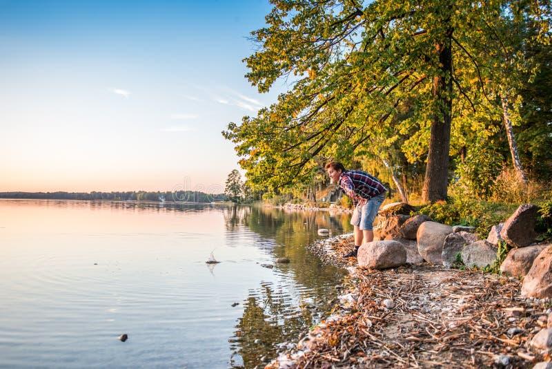 Ευτυχές άτομο κοντά στο παιχνίδι λιμνών με τις πέτρες στοκ εικόνες με δικαίωμα ελεύθερης χρήσης