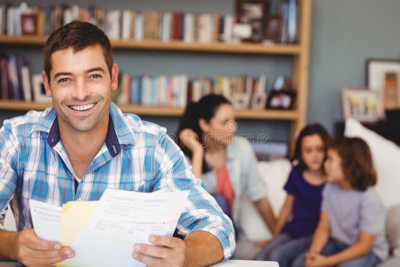 Ευτυχές άτομο με τα έγγραφα ενώ οικογενειακή συνεδρίαση στο υπόβαθρο στοκ εικόνα