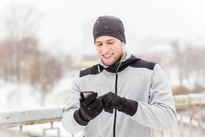 Ευτυχές άτομο με τα ακουστικά και smartphone το χειμώνα στοκ εικόνες