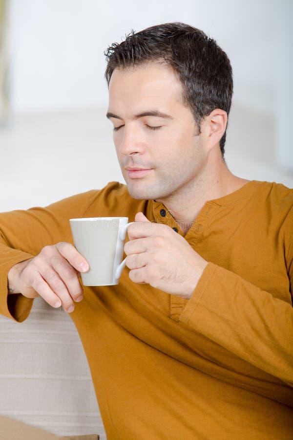 Ευτυχές άτομο με το τσάι φλυτζανιών στο σπίτι στοκ φωτογραφία με δικαίωμα ελεύθερης χρήσης