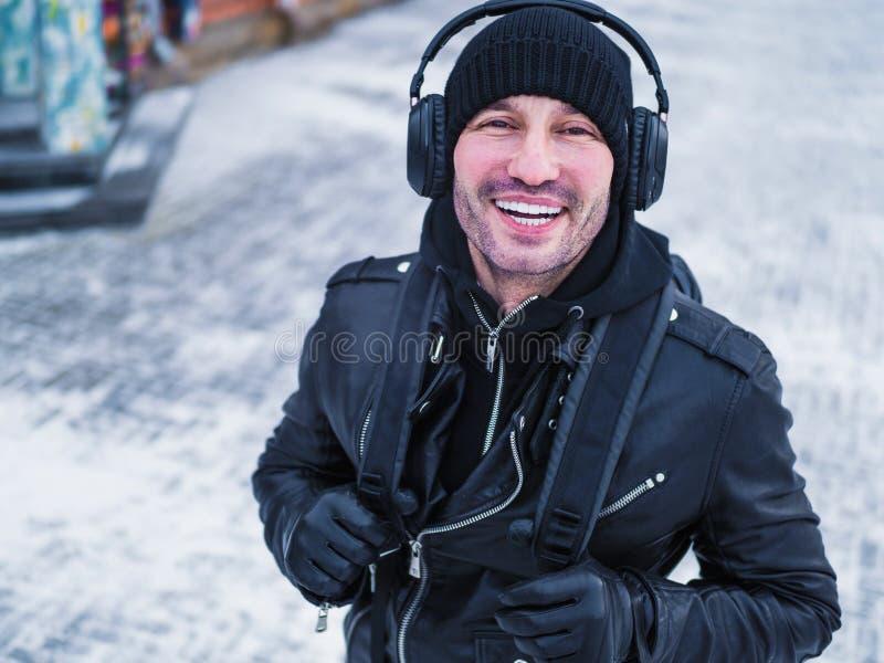 Ευτυχές άτομο που ακούει τη μουσική από ένα έξυπνο τηλέφωνο με ένα υπόβαθρο πόλεων ηλιοβασιλέματος ζεστασιάς στοκ φωτογραφία