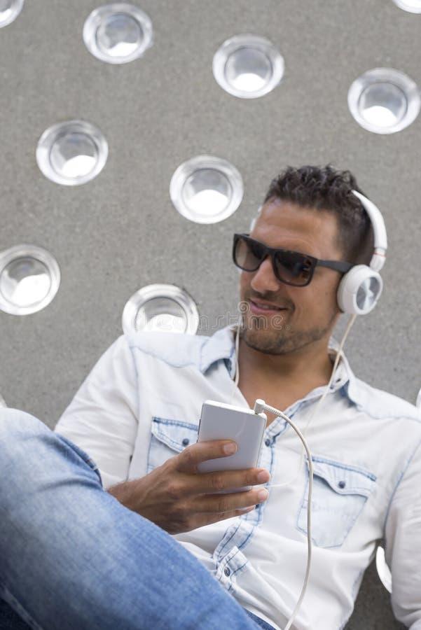 Ευτυχές άτομο που ακούει τη μουσική από μια έξυπνη τηλεφωνική εστίαση στο phon στοκ φωτογραφία