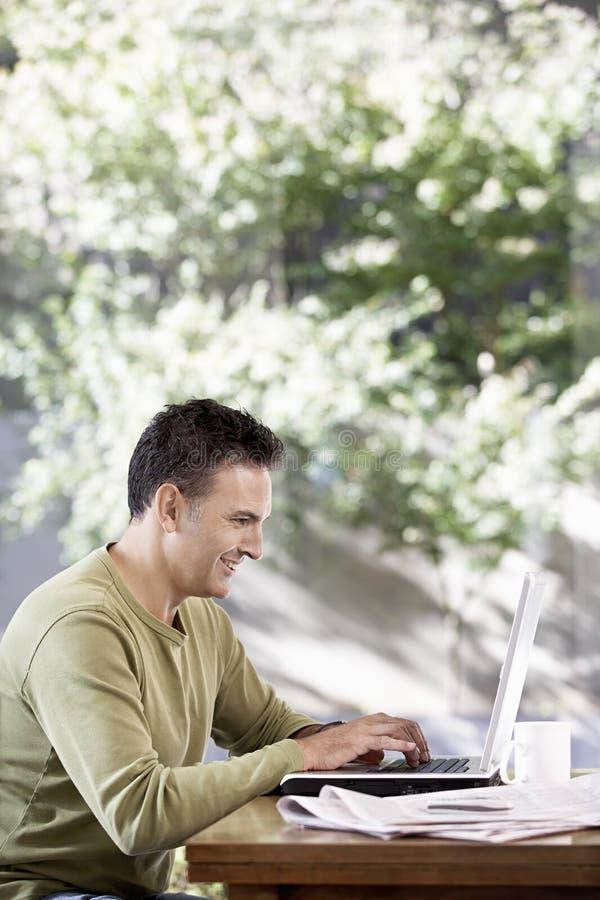 Ευτυχές άτομο που εργάζεται στο lap-top στοκ φωτογραφία με δικαίωμα ελεύθερης χρήσης