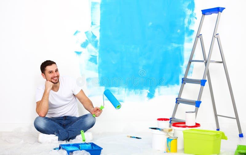 Ευτυχές άτομο που κάνει τις επισκευές, τοίχος χρωμάτων στο σπίτι στοκ εικόνα με δικαίωμα ελεύθερης χρήσης