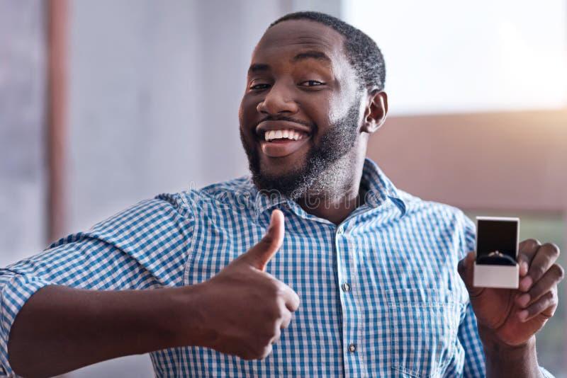 Ευτυχές άτομο που κρατά ένα δαχτυλίδι αρραβώνων στοκ φωτογραφία με δικαίωμα ελεύθερης χρήσης