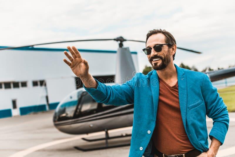 Ευτυχές άτομο που κυματίζει το χέρι του ενώ όντας δίπλα στο ελικόπτερο στοκ εικόνα με δικαίωμα ελεύθερης χρήσης