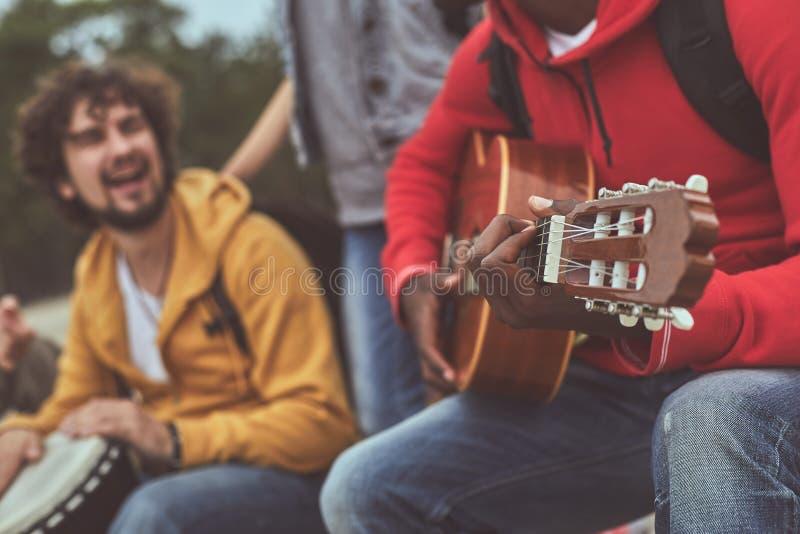 Ευτυχές άτομο που παίζει η συνοδεία φίλων του στο djembe στοκ εικόνες