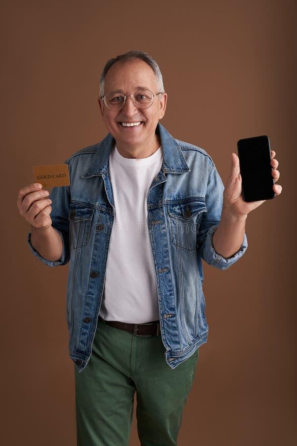 Ευτυχές άτομο που παρουσιάζει το σύγχρονο smartphone και χρυσή κάρτα στοκ εικόνα