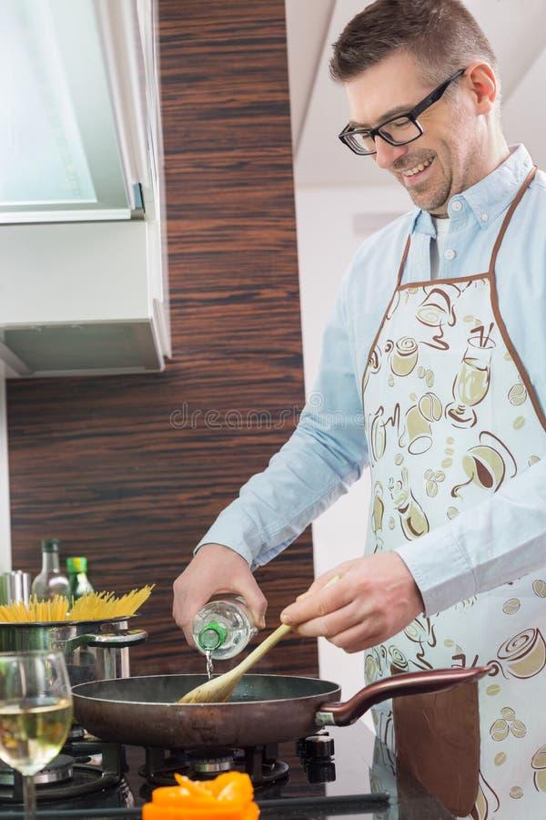 Ευτυχές άτομο που προσθέτει το άσπρο κρασί στην κατσαρόλλα μαγειρεύοντας στην κουζίνα στοκ φωτογραφία