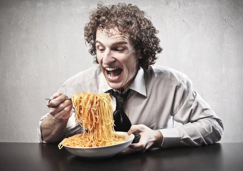 Ευτυχές άτομο που τρώει τα μακαρόνια στοκ φωτογραφία
