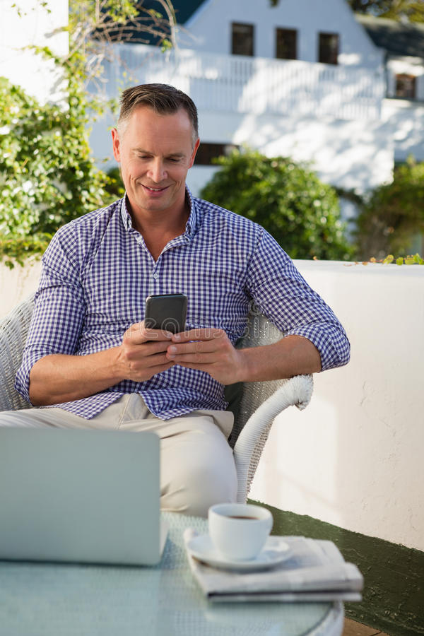 Ευτυχές άτομο που χρησιμοποιεί το κινητό τηλέφωνο καθμένος στον καφέ στοκ φωτογραφίες με δικαίωμα ελεύθερης χρήσης