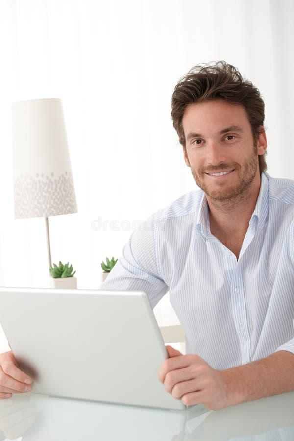 Ευτυχές άτομο στο σπίτι με τον υπολογιστή στοκ εικόνα