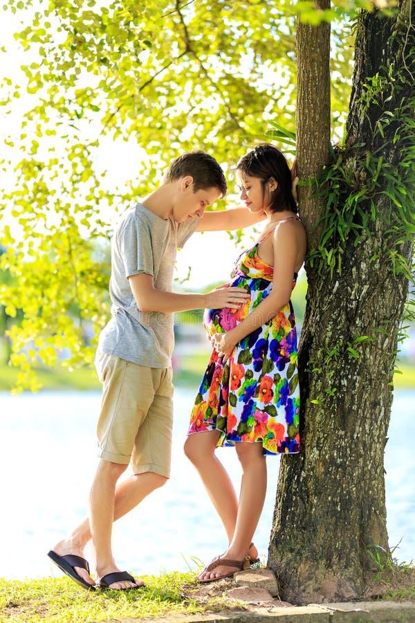 Ευτυχές έγκυο ζεύγος που στέκεται στο ttopical πάρκο στο πίσω φως στοκ φωτογραφίες