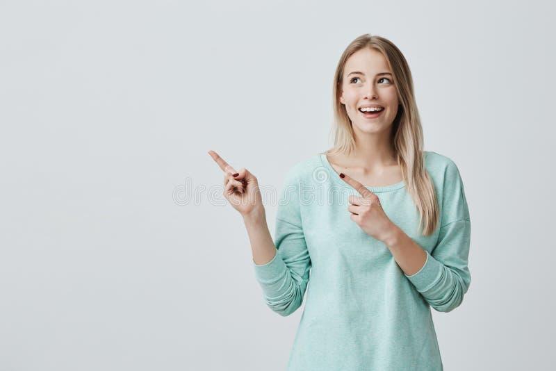 Ευτυχές έκπληκτο ξανθό νέο θηλυκό που χαμογελά ευρέως στη κάμερα, δείχνοντας τα δάχτυλα μακριά, που παρουσιάζουν κάτι που ενδιαφέ στοκ φωτογραφία με δικαίωμα ελεύθερης χρήσης