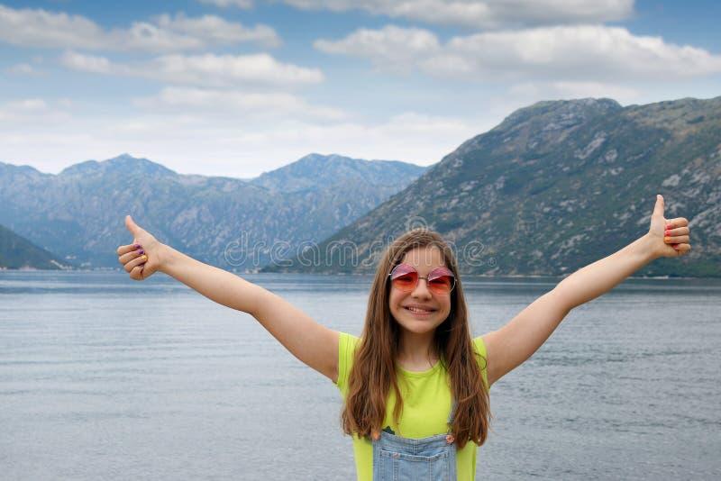 Ευτυχές έφηβη με τους αντίχειρες επάνω στον κόλπο Kotor θερινών διακοπών στοκ φωτογραφία με δικαίωμα ελεύθερης χρήσης