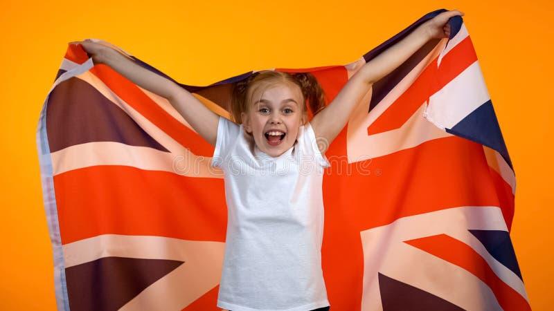 Ευτυχές έφηβη που κυματίζει τη βρετανική σημαία ενθαρρυντική για την αθλητική ομάδα, γλωσσικό σχολείο στοκ φωτογραφία με δικαίωμα ελεύθερης χρήσης