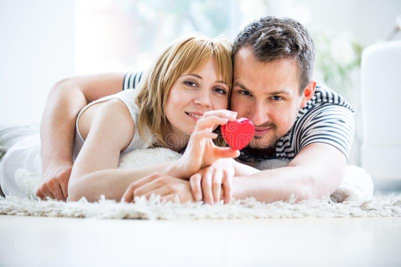 Ευτυχές αγαπώντας ζεύγος, κιβώτιο καρδιών υπό εξέταση στοκ φωτογραφίες