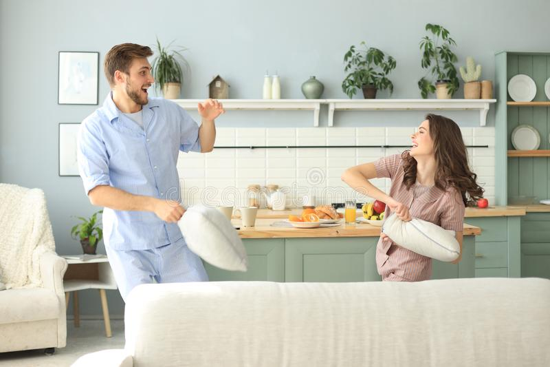 Ευτυχές αγαπώντας ζεύγος που έχει τη διασκέδαση ενώ έχοντας μια πάλη μαξιλαριών στο καθιστικό στοκ εικόνες
