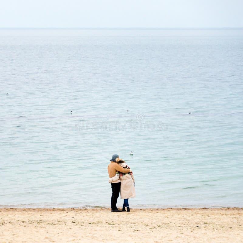 Ευτυχές αγαπώντας ζεύγος που αγκαλιάζει φορώντας τα θερμά ενδύματα που στέκονται στην ωκεάνια κρύα εποχή ακτών, ακροθαλασσιά, κεν στοκ εικόνες με δικαίωμα ελεύθερης χρήσης
