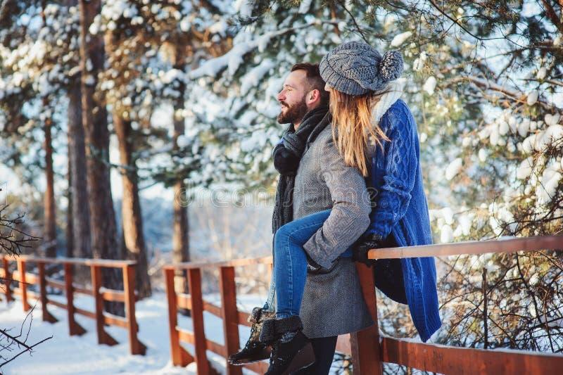 Ευτυχές αγαπώντας ζεύγος που περπατά στο χιονώδες χειμερινό δάσος, διακοπές Χριστουγέννων εξόδων από κοινού στοκ φωτογραφία