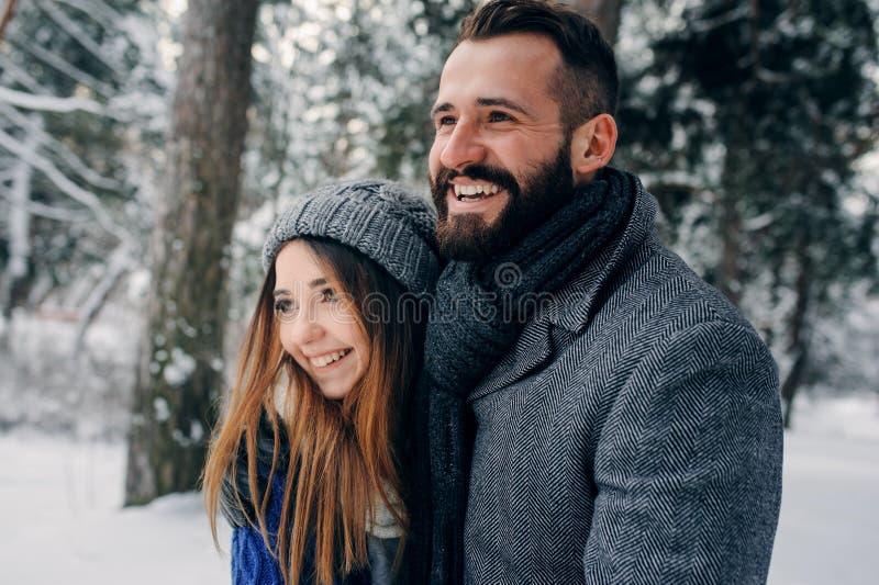Ευτυχές αγαπώντας ζεύγος που περπατά στο χιονώδες χειμερινό δάσος, διακοπές Χριστουγέννων εξόδων από κοινού Υπαίθριες εποχιακές δ στοκ φωτογραφία
