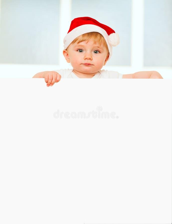 Ευτυχές αγοράκι στο καπέλο Santa με τον κενό πίνακα στοκ φωτογραφία