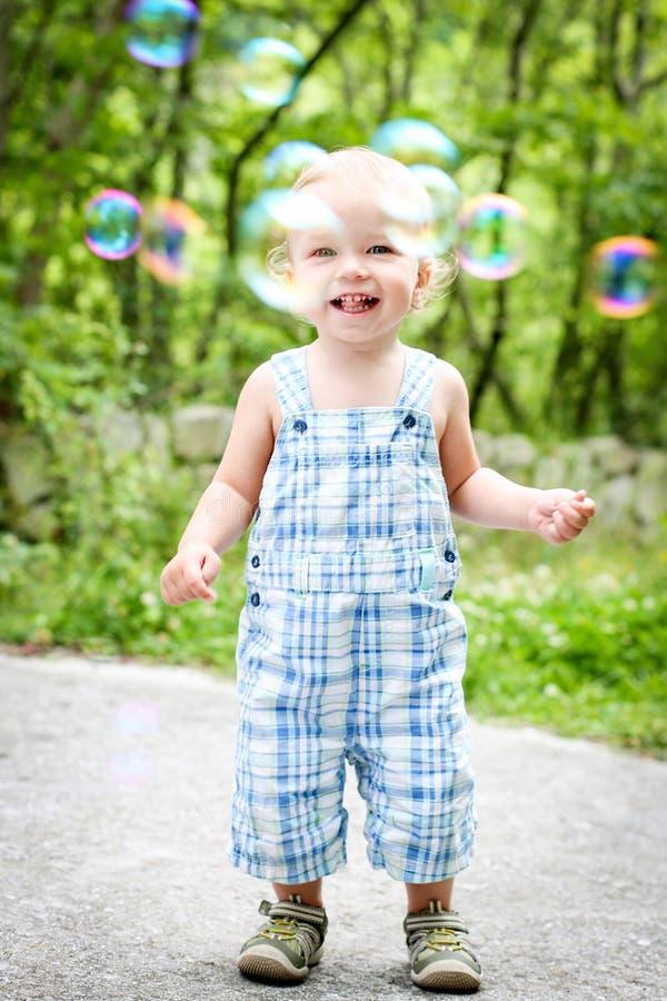 Ευτυχές αγόρι μικρών παιδιών που εξετάζει τις φυσαλίδες στοκ εικόνα με δικαίωμα ελεύθερης χρήσης