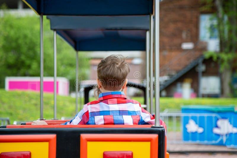 Ευτυχές αγόρι παιδιών που έχει τη διασκέδαση στο πάρκο Λήψη ενός γύρου στο τραίνο μωρών στοκ φωτογραφία
