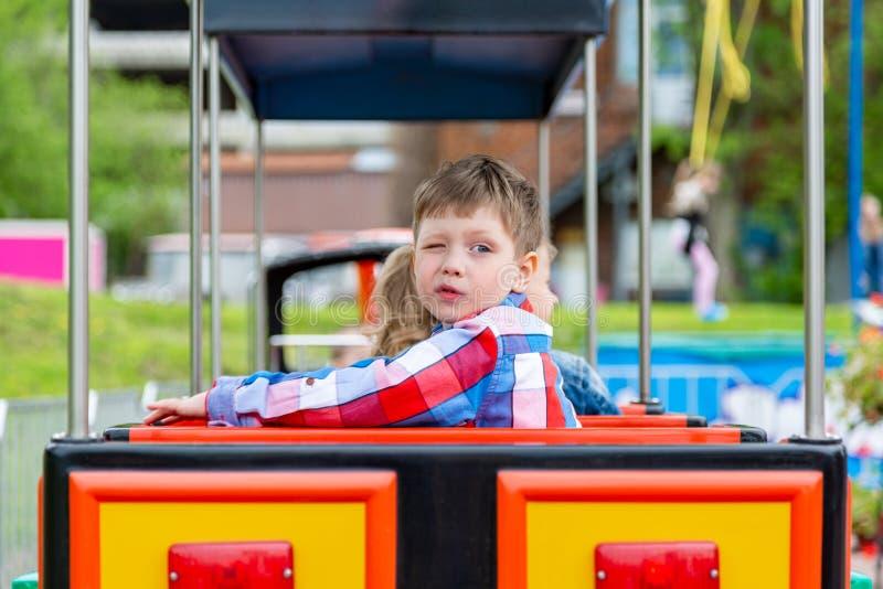 Ευτυχές αγόρι παιδιών που έχει τη διασκέδαση στο πάρκο Λήψη ενός γύρου στο τραίνο μωρών στοκ φωτογραφία με δικαίωμα ελεύθερης χρήσης