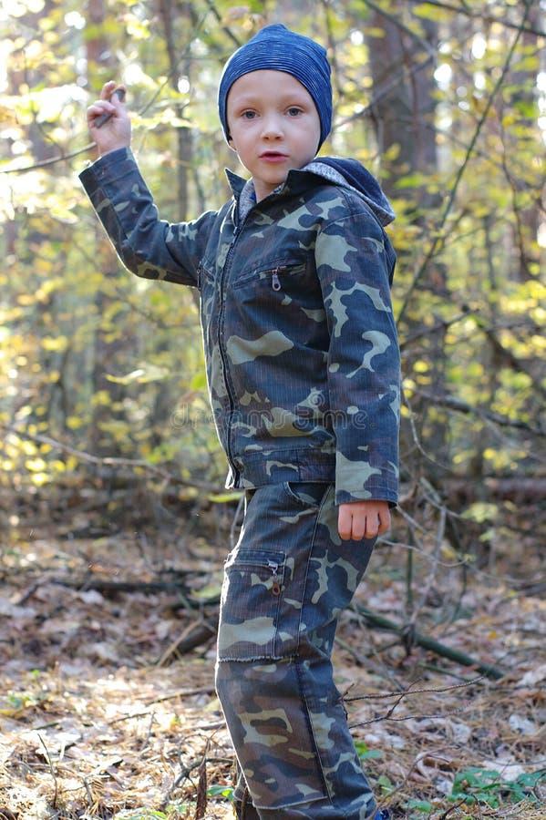 Ευτυχές αγόρι παιδιών στα ξύλα που ψάχνουν τα μανιτάρια Το αγόρι φορά μια κάλυψη ομοιόμορφη στοκ εικόνα με δικαίωμα ελεύθερης χρήσης