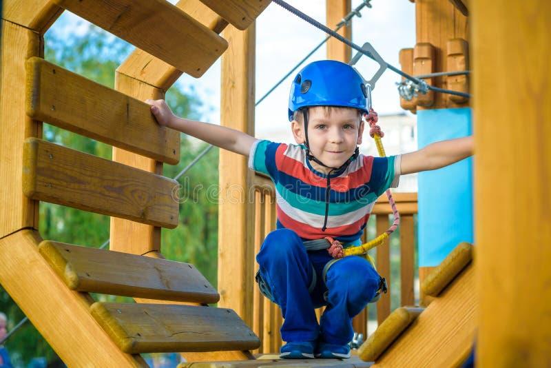 Ευτυχές αγόρι που έχει τη διασκέδαση και που παίζει στο πάρκο περιπέτειας, που κρατά τα σχοινιά και που αναρριχείται στα ξύλινα σ στοκ φωτογραφία